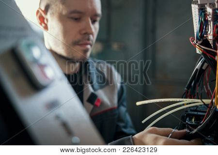 Portrait Of Electrician On Overalls Is Working With Energy Panel And Machinery Equipment On Plant -