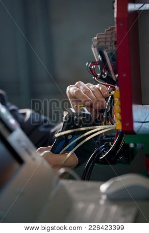 Hands Of Electrician With Stripper Installing Energy System On Machinery Industry, Close Up
