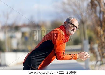 An Athletic Senior Male Leaning On Fence