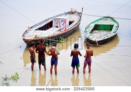 Boats And Unknown Children Inside The Waters Of The Ganges River In Varanasi. August 20, 2010