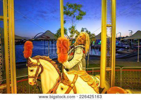 Happy Blonde Caucasian Woman Riding On White Horse Of Elizabeth Quay Carousel, Esplanade In Perth, W
