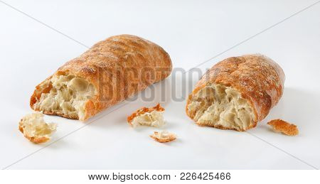 two pieces of fresh ciabatta bread on white background