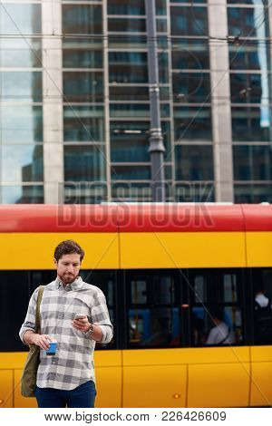 Young Man Sending A Text Message On A Cellphone And Drinking A Coffee While Standing Near A Bus Stop