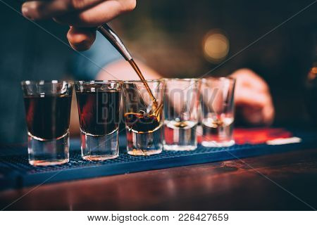 Bartender Pouring And Serving Alcoholic Drinks At Bar