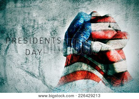 the clasped hands of a young man, patterned with the flag of the United States, and the text presidents day with a textured effect