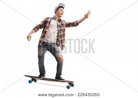 Full length portrait of a teenage hipster riding a longboard and making a peace sign isolated on white background