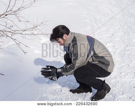 Cheerful Handsome Man In Outerwear Throwing Snowball Posing At Camera In Sunlight.