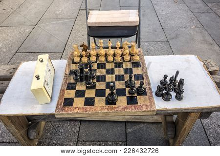 Old Wooden Chessboard, Shabby Wooden Chess Pieces And A Chess Clock Are Located On A Homemade Table