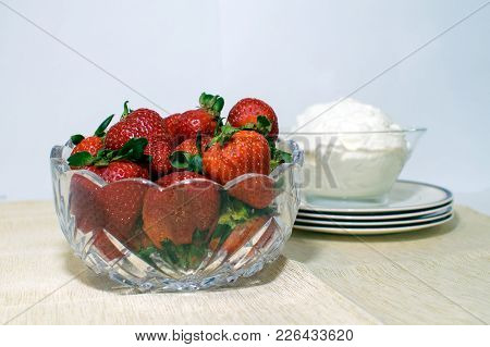 A Glass Bowl Filled With Strawberries And Another One With Whipped Cream.