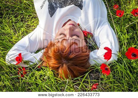 Young And Beautiful Caucasian Girl Lying At The Red Anemone Flower Meadow. Day Dreaming, Relaxation