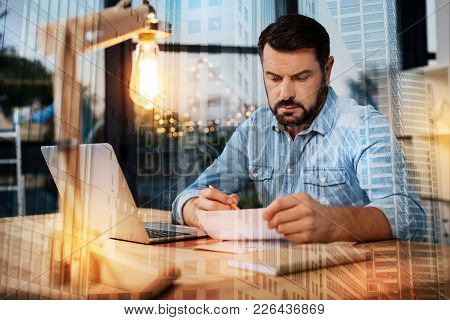 Interesting. Serious Young Attentive Man Sitting At The Table And Feeling Interested While Reading A