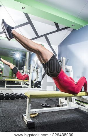 Man In The Gym Doing Leg And Back Workout With His Legs Raised In The Air