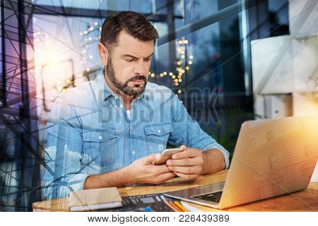 Very Strange. Serious Bearded Worried Man Frowning And Looking Suspiciously At The Screen Of His Lap