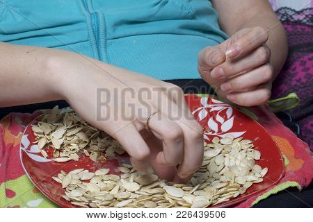 The Girl Is Eating Pumpkin Seeds. Seeds Lie On A Plate, Next To It Lies The Husks.