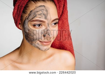 A Lovely Young Girl With A Red Towel On Her Head Applied A Useful Clay Mask To Half The Face