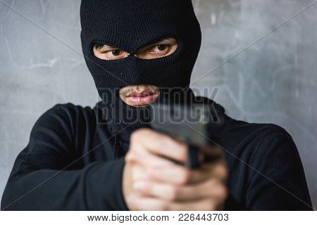 Male Criminal Attacking With Hand Gun Pointing Gun To Target In Front, Robber Concept