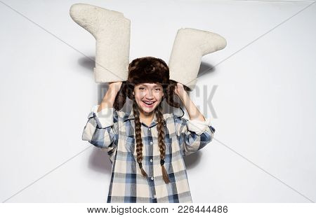 Happy Russian Girl In A Warm Hat With Ear-flaps Holds Gray Felt Boots In Hands