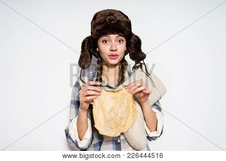 Lovely Russian Girl In A Hat With Ear-flaps Holds A Pancake In Her Hands, Celebrates Shrovetide