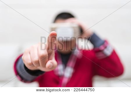Man Wearing Vr Glasses Or Virtual Reality Headset With His Finger Feeling The Simulation World At Ho