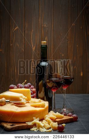 Whole Round Head Of Parmesan Or Parmigiano Hard Cheese And Wine On Concrete Background Or Table