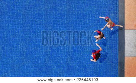 Two Little Boys And Girl Fun Jumping Into The Swimming Pool, Summer Holidays And Vacation Concept, T
