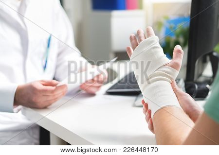 Injured Patient Showing Doctor Broken Wrist And Arm With Bandage In Hospital Office Or Emergency Roo