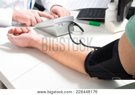 Doctor Or Nurse Measure Blood Pressure Of A Patient With Meter And Monitor Device. Hand And Arm On E