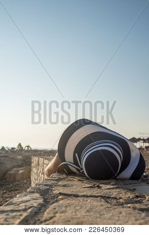 Woman In A Large Sunhat Sunbathing On A Beach On Summer Vacation In Travel Concept.
