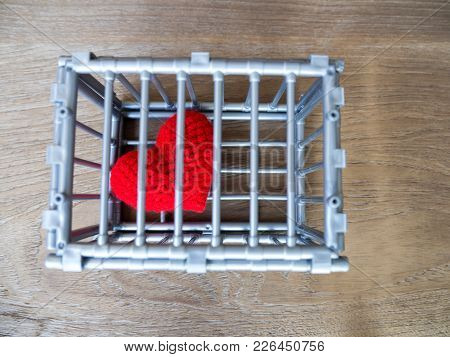 Heart In The Cage Put On A Wooden Table, It Shows The Closure Of Freedom And Love. Love Is Disappoin