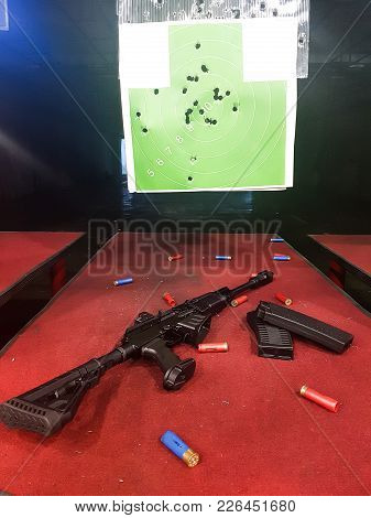 Picture Of Shooting Gallery With Target, Gun On Brown Table