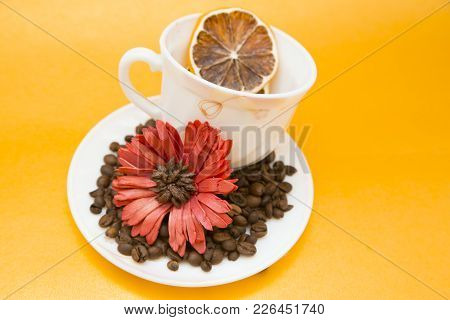 White Cup With Saucer With Coffee Beans, Red Flower And Orange Slice, Yellow Background, Copy Space,