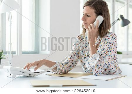 Side View Of A Woman Dialing Telephone Number