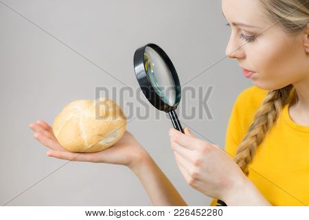 Woman Holding Bun Bread Roll And Magnifying Glass Examine Wheat Product Ingredients