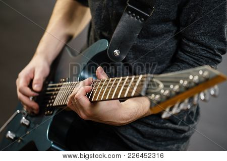 Male Hands With Electric Guitar. Close Up, Part Body Adult Person Is Holding Instrument And Playing.