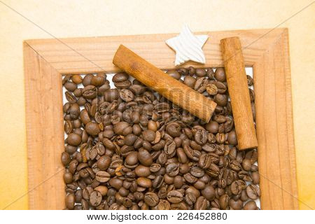 Wooden Photo Frame Filled With Coffee Beans, Cinnamon Sticks And A Decorative Star On The Table With