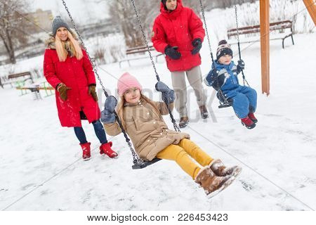 Photo Of Girl And Boy Swinging In Winter On Swing In Park With Parents