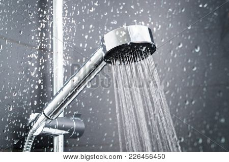 Fresh Shower Behind Wet Glass Window With Water Drops Splashing. Water Running From Shower Head And