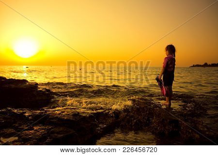 Little Caucasian Girlie On The Rock, With Sunset In Background. Croatian Cost, Seaboard. Summer, Tra