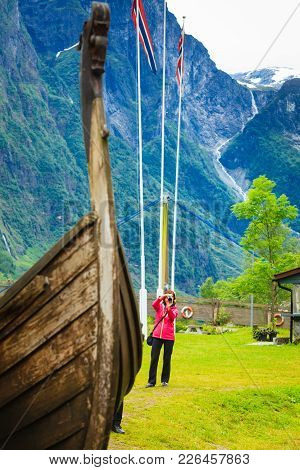 Female Tourist Standing Near Old Wooden Viking Boat In Norwegian Nature, Taking Photo With Camera. T