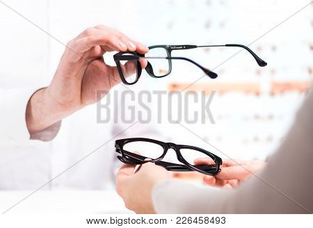 Optician Giving New Glasses To Customer For Testing And Trying. Eye Doctor Showing Patient Lenses In
