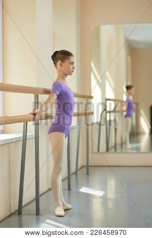 Girl Standing At Railing In Ballet Hall. Child Stretching Out Using Ballet Barre In Studio. Young Ba