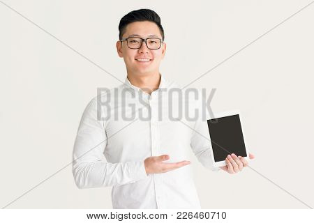 Satisfied Korean Salesman Presenting New Device And Looking At Camera. Jolly Excited Handsome Busine