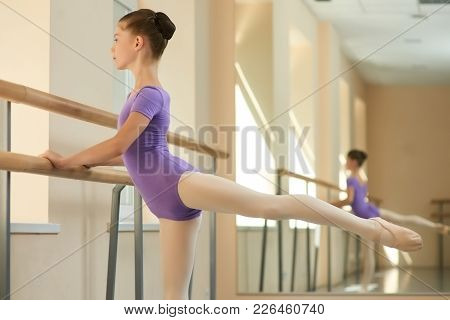 Young Ballerina Practice On Barre. Girl Stretching Out On Railing At Ballet Studio. Exercises Of Bal