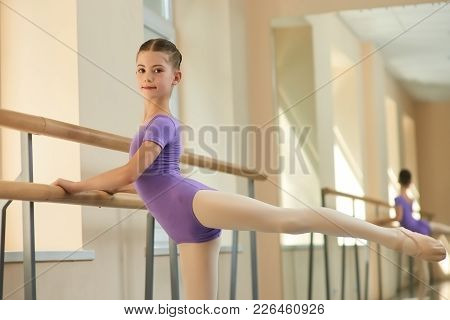 Ballerina Stretching Out And Looking At Camera. Young Beautiful Girl Is Training Stretch Of Her Leg