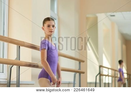 Young Beautiful Ballerina Posing In Studio. Caucasian Young Girl Standing Near Ballet Barre During B