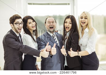 Boss And Triumphant Business Team Make The Gesture Of Thumb Up.photo On The Background Of Office