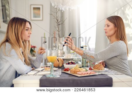 Serious attractive young woman showing her best friend her mobile phone as they sit enjoying a healt