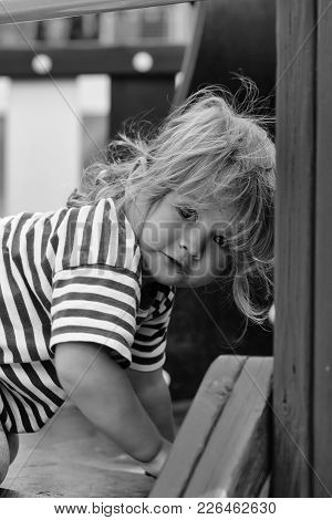 Cute Baby Boy With Blond Hair In Striped Blue Tshirt Climbing Stairs In Playhouse On Sunny Summer Da