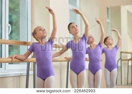 Young Ballerinas Rehearsing In Ballet Class. Group Of Young Ballerinas Performing Different Choreogr