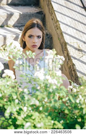 Young Girl Pose At Blossoming Bush On Sunny Day, Summer. Woman Beauty, Makeup, Look. Youth, Freshnes